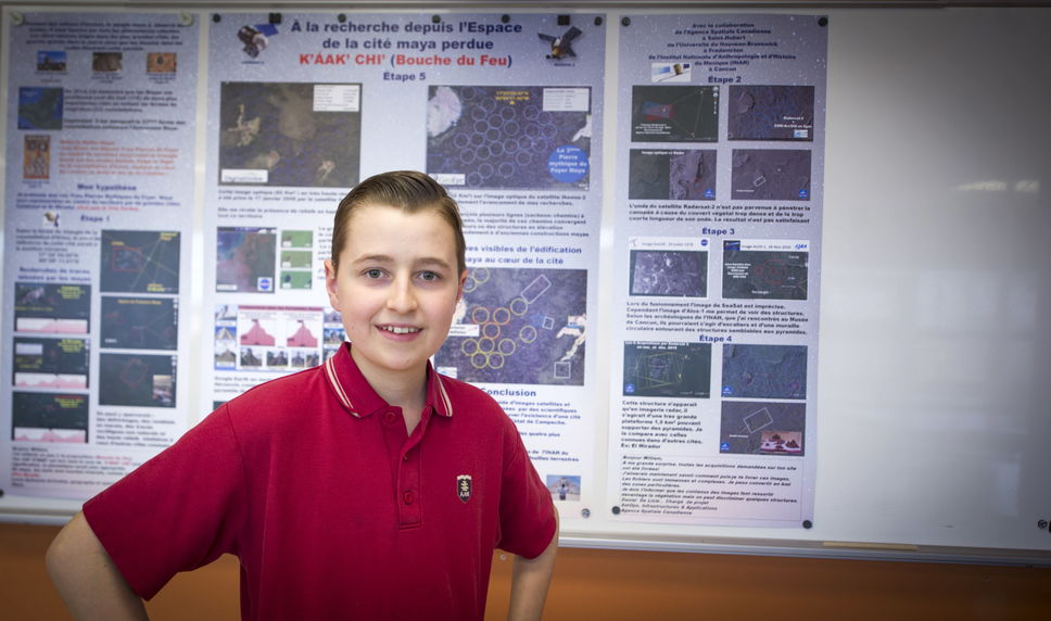 Wiiliam Gadoury in front of a poster presentation of his research.